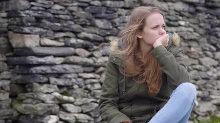 be sad : Young woman sits on the ground - seems to be sad