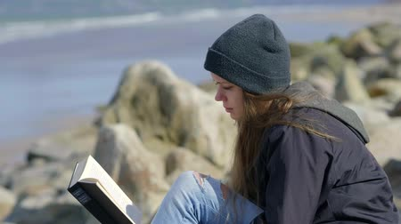 przyjaźń : Young woman sits at the ocean while reading a book Wideo