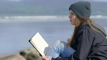 irlanda : Young woman relaxes while reading a book in the nature