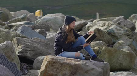 pobřežní : Young woman sits on a rough coast and reads in a book