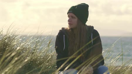 kamış : Girl sits in reed grass and loves the country of Ireland Stok Video
