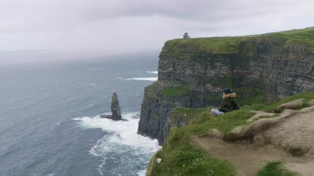tek başına : Young woman sits alone at the Cliffs of Moher Stok Video