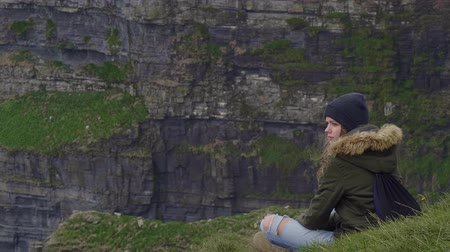 roccioso : Perfect place to relax - girls sits on the top of the Cliffs of Moher Filmati Stock