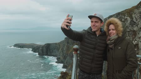 selfie girl : Young couple stands at the steep cliffs of Ireland and take a selfie
