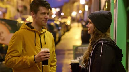 amigos : Two friends in front of an Irish pub drinking beer