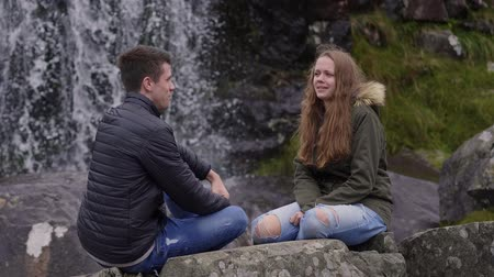 maravilhoso : Two friends enjoy the wonderful nature of Ireland in front of a waterfall