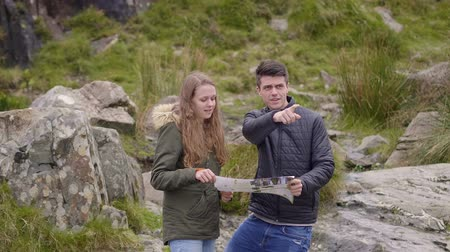 kerry : Two friends on a sightseeing tour - checking directions on a map Stock Footage
