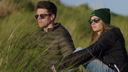 kamış : Young couple enjoys the sunset over the ocean while sitting in reed grass