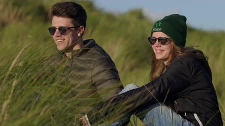 kamış : Happy couple sits in the reed grass and enjoys the sunset over the ocean