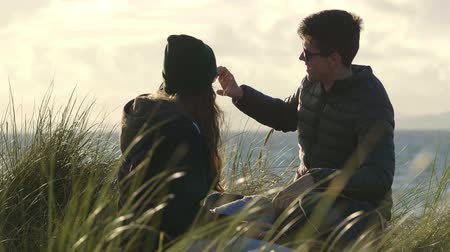 kamış : Pretty couple sits at the high reed grass at the beach Stok Video