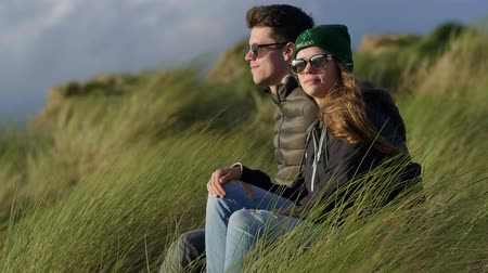 kamış : Happy couple relaxes at the ocean while sitting in reed grass Stok Video