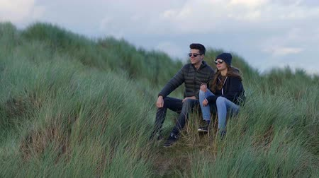 gramíneo : Two friends sit on the grassy dunes of Irelands west coast