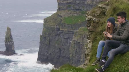 kerry : Two friends travel to Ireland - sitting on the top of the Cliffs of Moher Stock Footage