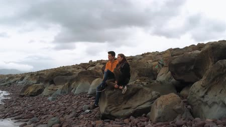 kerry : Two friends sit on a rock and look over the ocean Stock Footage