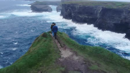 atlântico : Young couple walks to the edge of a cliff at the Irish west coast Vídeos