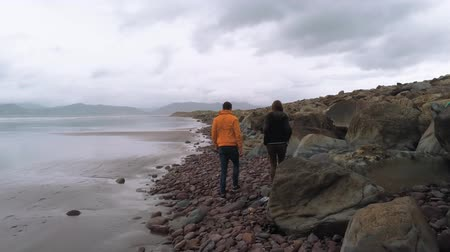 irsko : Two friends walk along a pebbly beach at the Irish west coast