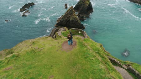 rocky mountains : Young couple stands on the top of Dunquin Pier in Ireland Stock Footage