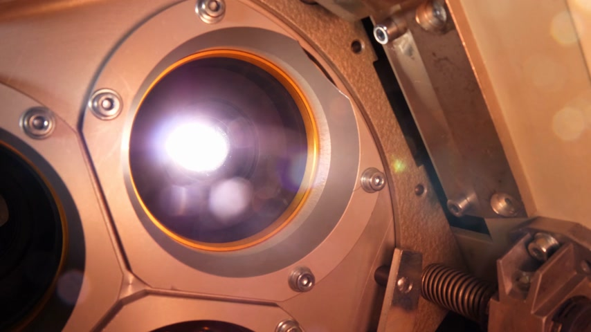filmmaker : The lens of a cinema projector in a movie theater - close up view