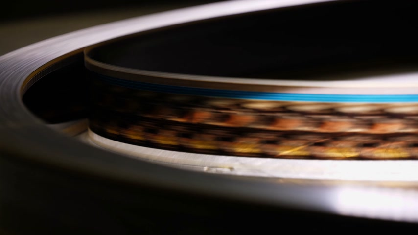 filmmaker : Close up of a moving 35mm film stripe in a movie theater