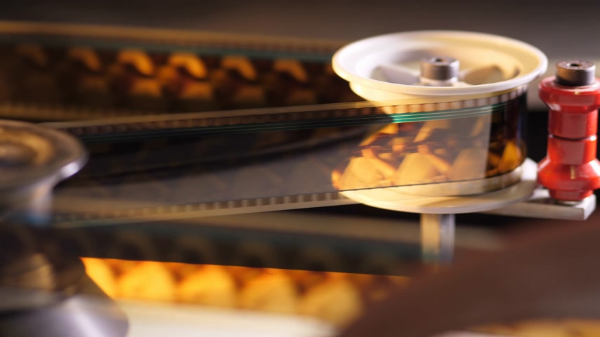 filmmaker : Vintage 35mm film running through a cinema projector in a movie theater Stock Footage