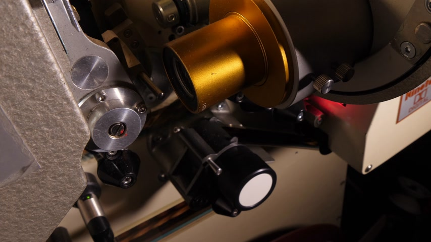 cinematography : Film runs through a 35mm projector in a movie theater Stock Footage