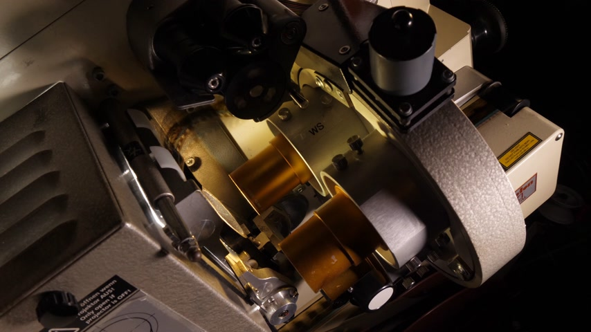 on camera : Close up of a 35mm cinema projector in a movie theater