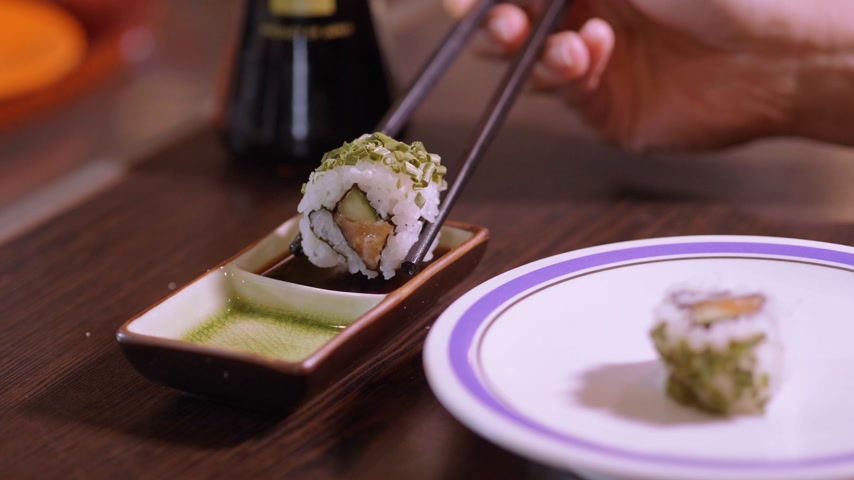 sushirestaurant : Dipping sushi rolls into soy sauce