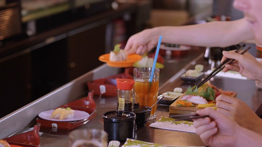 salsa de soya : Eaiting Sushi recién hecho en un Running Sushi Bar Archivo de Video