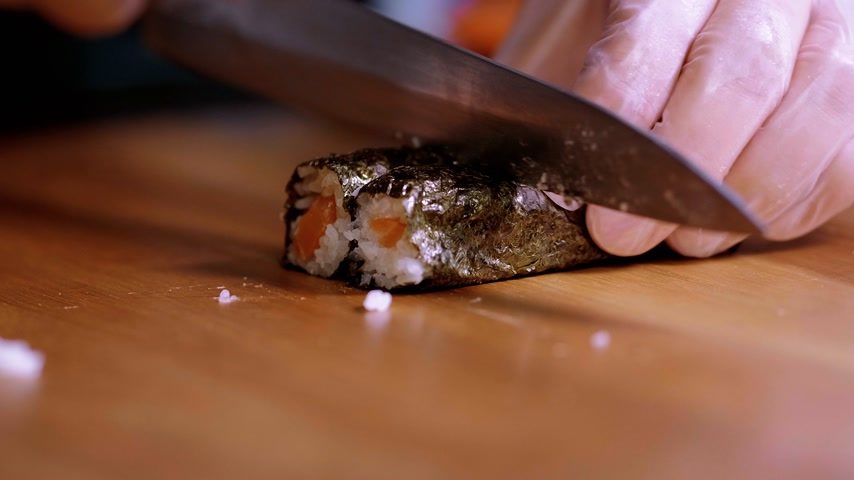 krewetki : Cutting freshly made Sushi rolls into pieces - Asian restaurant