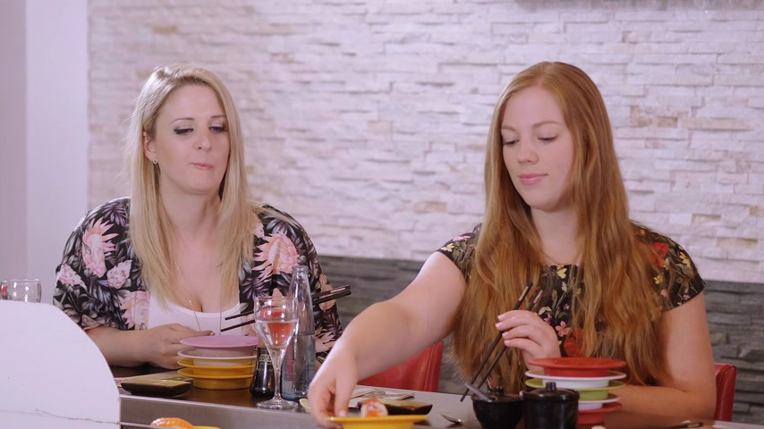 heathy : Two beautiful girls eat Sushi at a bar