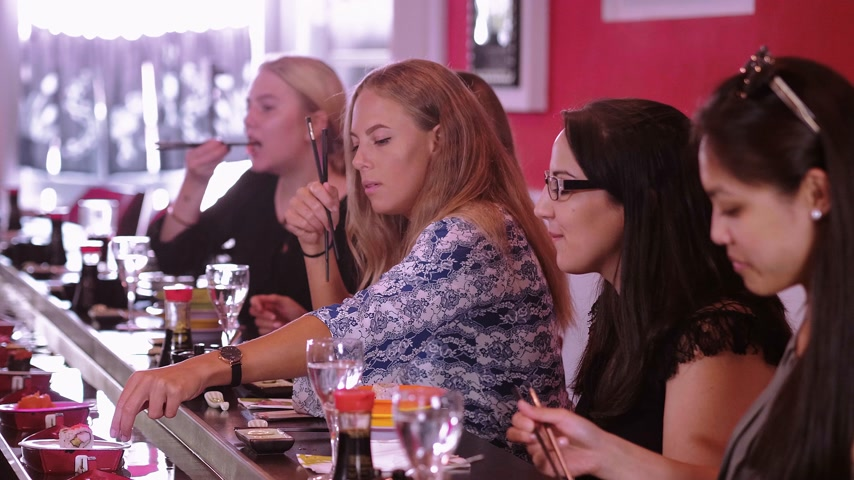 heathy : A group of girls sit in a Sushi Bar restaurant and eat Asian food Stock Footage