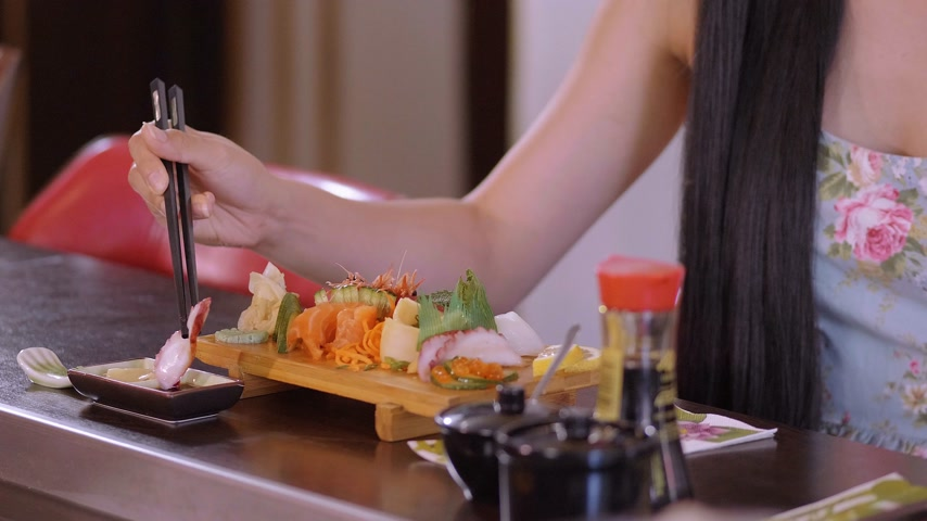 camarão : Young Asian girl eats Sushi