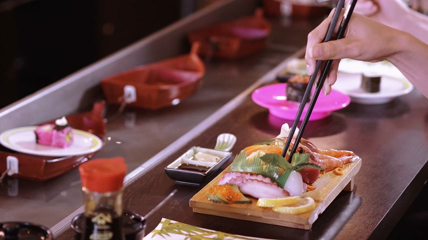 atum : Eating Sushi with chopsticks in a Asian restaurant - close up shot Stock Footage