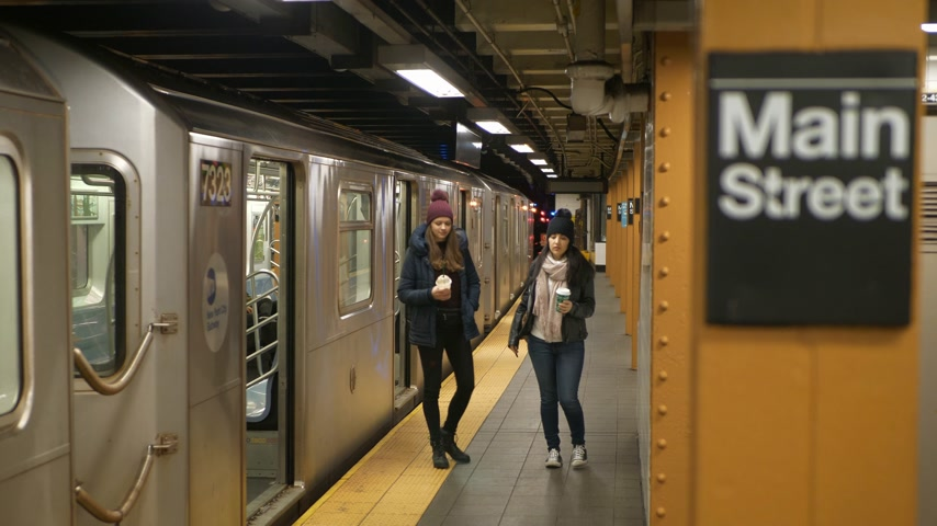jabłka : Two women on a platform of a New York subway station wait for their train