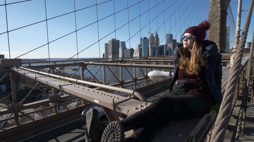 maravilhoso : Young beautiful woman on Brooklyn Bridge New York enjoys a wonderful sunny day Stock Footage