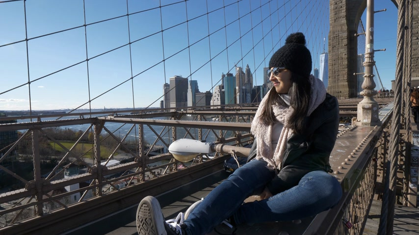 aro : Young and reckless girl sits on the rim of Brooklyn Bridge New York