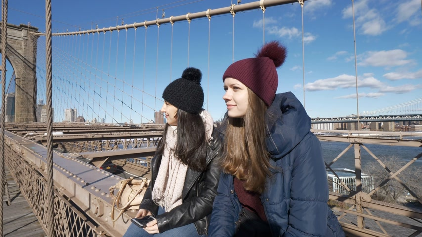 taxi : Two girls walk over the famous Brooklyn Bridge in New York