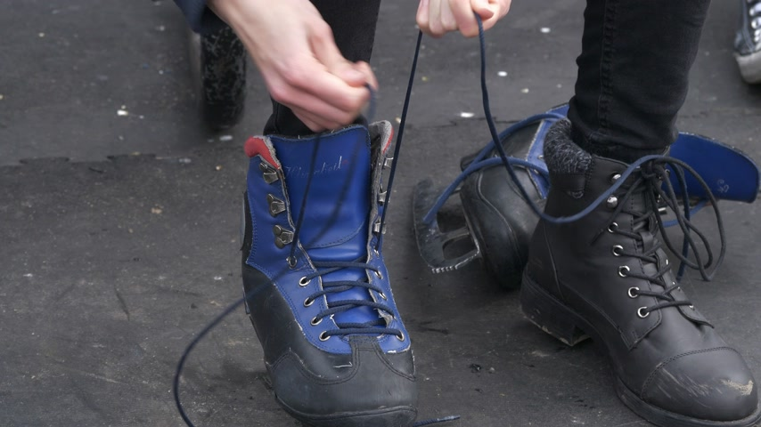 patenci : Young skater puts on the ice skating shoes