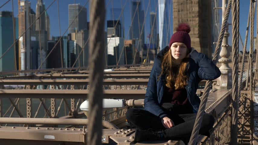 samochody : Beautiful girl on Brooklyn Bridge enjoys a sunny day while relaxing