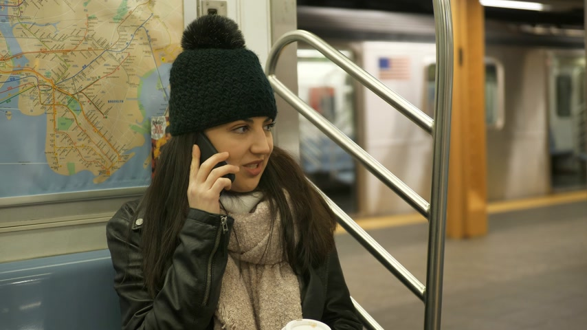 apple park : Young woman takes a phone call in a New York subway train Stock Footage