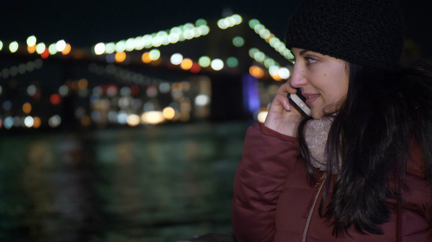 jabłka : Young woman takes a phone call at Brooklyn Bridge by night Wideo