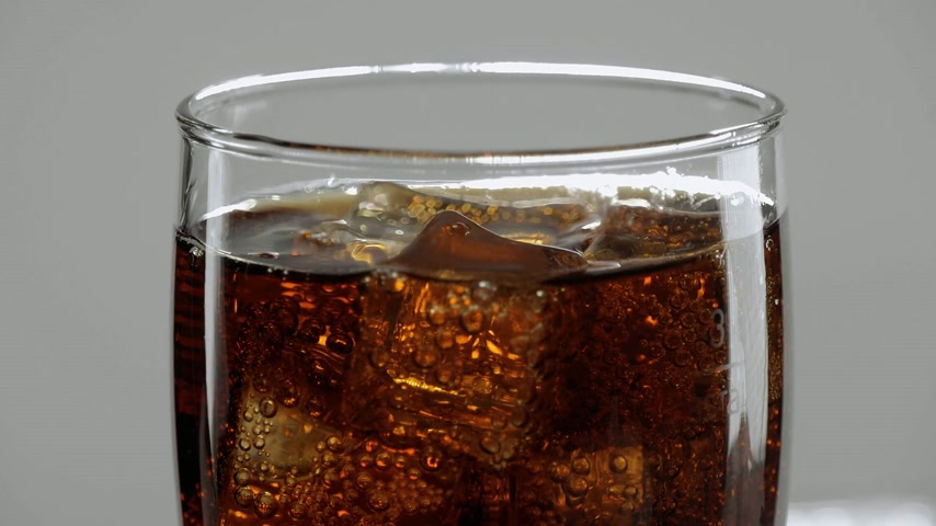 foods : Amazing close up shot of a glas of Cola with ice cubes - refreshing soda in slow motion Stock Footage
