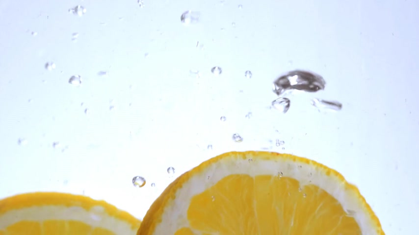 cytryna : Close up shot of orange slices falling into water