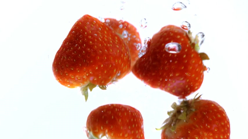 come : Slow motion shot of strawberries falling into water - very refreshing