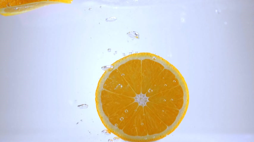 come : Orange slices fall into water in slow motion