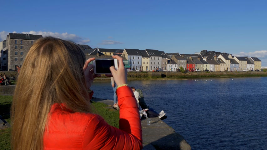 v řadě : Young woman takes photos of the colorful houses in Galway Claddagh - GALWAY, IRELAND - MAY 11, 2019 Dostupné videozáznamy