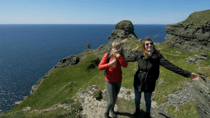 eire : Two friends walk along the steep cliffs of the Irish west coast Stock Footage