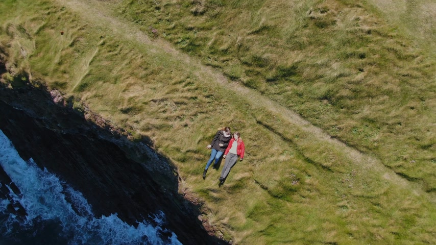 gyrophare : Two girls lying in the grass at the cliffs of the Irish coast - drone view from above