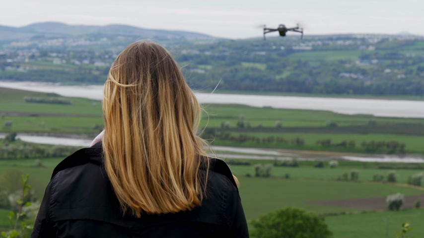 irsko : Young woman flying a drone in Ireland Dostupné videozáznamy