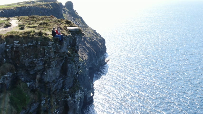 kelt : Two girls sit on the edge of the famous Cliffs of Moher in Ireland Stok Video